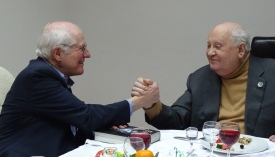 Photo of the author clasping right hands with Mikhail Gorbachev while both are seated at lunch table. Author's left hand rests on a copy of his biography of Gorbachev.